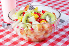 Fruit salad in a glass bowl, yogurt, white napkin. Fruit salad in a glass bowl, yogurt, white napkin, fork on a red and white tablecloth Stock Photography