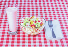 Fruit salad in a glass bowl, yogurt, white napkin. Fruit salad in a glass bowl, yogurt, white napkin, fork on a red and white tablecloth Royalty Free Stock Image