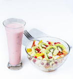 Fruit salad in a glass bowl, yogurt, white napkin. Fruit salad in a glass bowl, yogurt, white napkin and fork on a white surface Royalty Free Stock Images