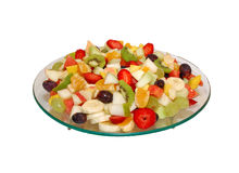 Fruit salad on glass plate. Fruits are bite size . White isolated backround royalty free stock photography