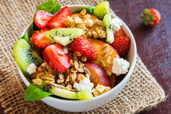 Fruit salad with granola. Fresh fruit salad with granola, feta cheese and honey in bowl for healthy breakfast Royalty Free Stock Images