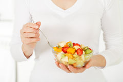 Fruit salad in the hands of women. Royalty Free Stock Photo
