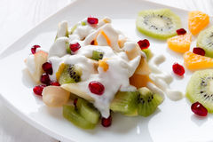 Fruit salad with ice cream on a white plate closeup Royalty Free Stock Photography