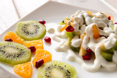 Fruit salad with ice cream on a white plate Royalty Free Stock Photos