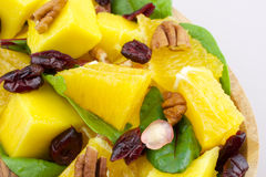 Fruit salad. Mango, orange, pomegranate, nuts, cranberries - on wooden plate Stock Photos
