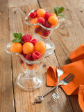 Fruit salad with melon balls and raspberries in glass bowl. Selective focus Stock Images