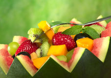 Fruit Salad in Melon Bowl. Fresh fruit salad (strawberry, kiwi, mango, grape) in melon bowl with kiwi and mango on fork and a mint leaf as garnish in front of Stock Photos