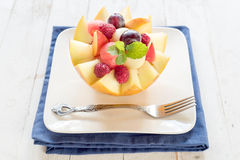 Fruit salad in melon Stock Images