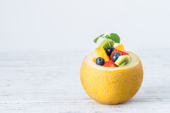 Fruit salad in melon on wooden table. Copy space Stock Images