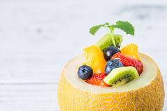 Fruit salad in melon on wooden table. Copy space Stock Photo