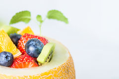Fruit salad in melon on wooden table. Copy space Royalty Free Stock Image