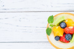 Fruit salad in melon on wooden table. Copy space, top view Stock Images