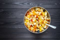 Fruit salad in metal bowl with spoon on dark background stock photography