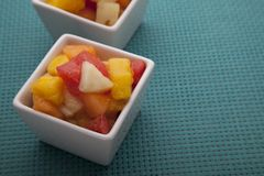 Fruit salad mix of melon, banana, watermelon, orange and pineapple in a small porcelain bowl Royalty Free Stock Image