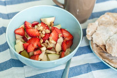 Fruit salad with nuts. Fruit salad with strawberry, apple, banana and walnuts in a blue bowl Stock Photos