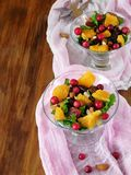 Fruit salad with orange pieces, cranberries and arugula Royalty Free Stock Image