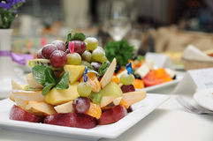 Fruit salad on a plate. Fruit salad (grape, apple, pear, orange, mix) on a plate in fine restaurant royalty free stock images