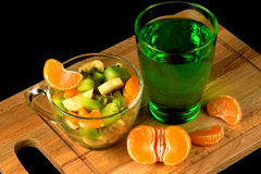 Fruit salad, segments of tangerine and glass with drink Royalty Free Stock Photography