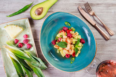 Fruit salad with shrimp, avocado, bulgarian pepper, kiwi, pineapple, raspberries in plate on wooden background close up Royalty Free Stock Photos