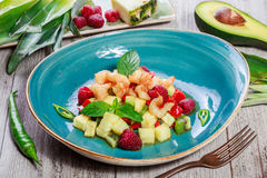 Fruit salad with shrimp, avocado, bulgarian pepper, kiwi, pineapple, raspberries in plate on wooden background close up. Royalty Free Stock Photo