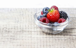 Fruit salad in small transparent bowl on wooden table Royalty Free Stock Photo