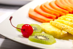 Fruit salad. Some fruits on a white dish, kiwi and a cherry in focus and  pineapple out of focus Royalty Free Stock Image