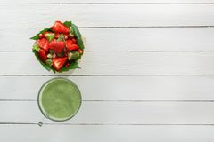 Fruit salad of strawberries, kiwi and pomegranate in a wicker basket and fresh green smoothies with lime and mint in a glass. View from above. The concept of a royalty free stock photo