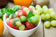 Fruit salad with strawberries, oranges, kiwi, grape and watermel. On in blow on wood background Stock Photography