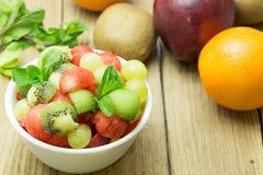 Fruit salad with strawberries, oranges, kiwi, grape and watermel. On on wood background Stock Image