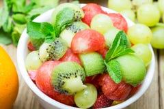 Fruit salad with strawberries, oranges, kiwi, grape and watermel. On on wood background Royalty Free Stock Photo