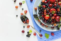 Fruit salad with strawberry, blueberry, cherry, gooseberry and black currant on wooden gray background Royalty Free Stock Photography