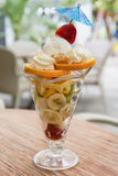 Fruit salad in sundae cup with bananas, oranges and kiwi Stock Images