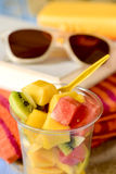 Fruit salad, sunglasses, book and beach towel Royalty Free Stock Image