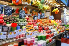 Fruit Salad and tropical fruits arranged in plastic cups on a market stall Stock Image