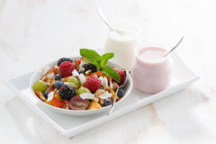 Fruit salad and various yoghurt on a white wooden table. Horizontal royalty free stock photos