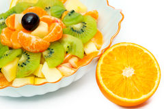 Fruit salad in vase and orange Royalty Free Stock Image