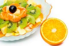 Fruit salad in vase and orange. Fruit salad in white vase and orange Royalty Free Stock Image