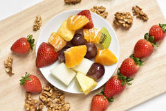 Fruit salad and walnuts. High-angle shot of a white ceramic plate with a fruit salad, made with orange, melon, kiwi, pineapple, grapes and strawberries, and some royalty free stock photos