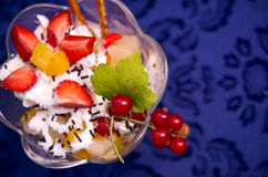 Fruit Salad with Whipped Cream. Overhead view of fruit salad with strawberries, peaches, red grapes and whipped cream on a blue tablecloth Stock Image
