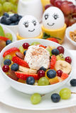 Fruit salad with whipped cream and painted eggs for breakfast Royalty Free Stock Images