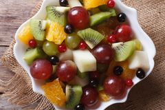 Fruit salad in white plate close-up horizontal top view, rustic Royalty Free Stock Image