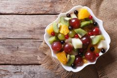 Fruit salad in white plate horizontal top view, rustic Stock Images