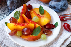 Fruit salad in white plate. Snack of fresh peaches, grapes, dogwood, plums, and mint leaves. Healthy Breakfast Royalty Free Stock Image