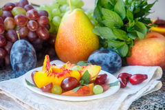 Fruit salad in white plate. Snack of fresh peaches, grapes, dogwood, plums, and mint leaves. Healthy Breakfast Royalty Free Stock Photo