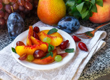 Fruit salad in white plate. Snack of fresh peaches, grapes, dogwood, plums, and mint leaves. Healthy Breakfast Stock Image