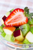 Fruit salad in white plate on tablecloth Royalty Free Stock Image