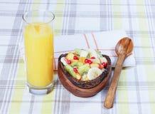 Fruit salad in a wooden bowl, orange juice. Royalty Free Stock Photos