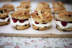 Fruit scones. Fresh baked fruit scones on a wooden board with raspberries and cream for sale in a Bakery royalty free stock photo