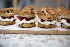 Fruit scones. Fresh baked fruit scones on a wooden board with raspberries and cream for sale in a Bakery Royalty Free Stock Photography