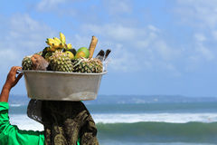 Fruit seller at the beach. In Kuta, Bali Indonesia. Old asian woman carrying the fruits for sale Royalty Free Stock Photos